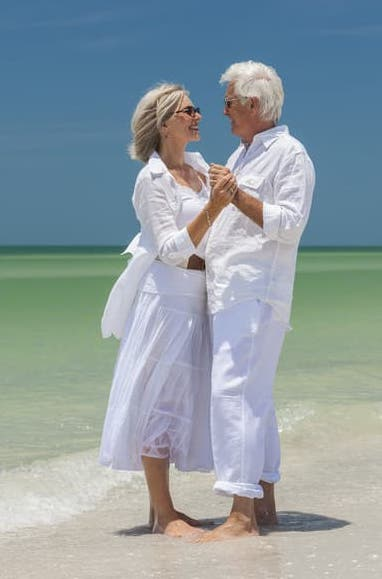 Older couple dressed in white dancing barefoot on a tropical beach