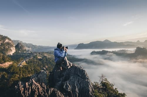 man on a mountain top taking a photograph