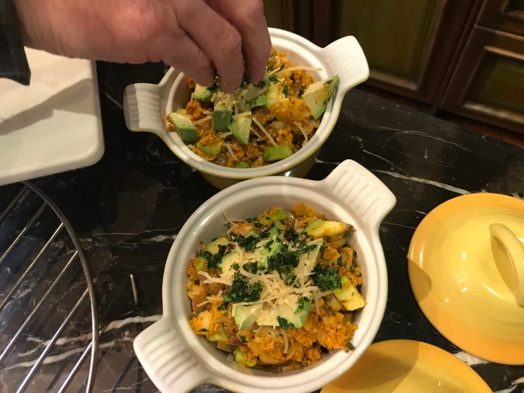 hand sprinkling cheese on a dish