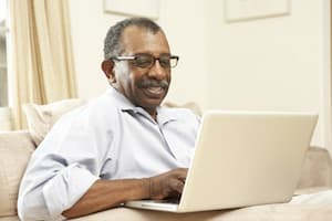 African American man smiling with a laptop
