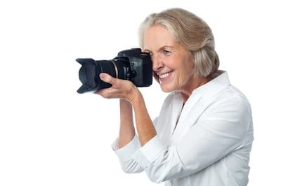 Happy older lady with camera