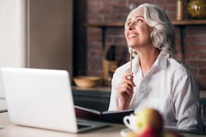 Older lady thinking at laptop