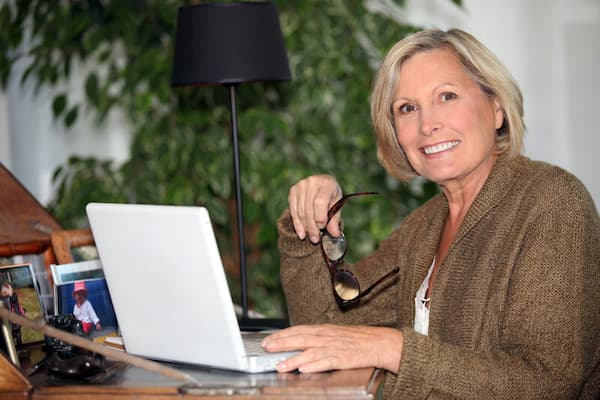 Smiling writer holding glasses at laptop