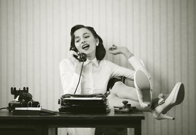Vintage photo of lady with feet on desk on phone