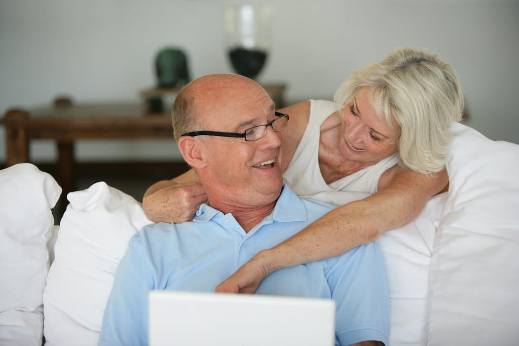 Affiliate Marketing for Retiress Older Couple Sitting on a Couch Laughing and Looking at a Laptop