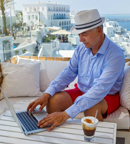 Elderly Man Writing on a Laptop in a Beautiful Location Overlooking the Sea