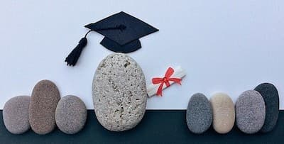 eight stones in a row with the middle one wearing a graduation cap
