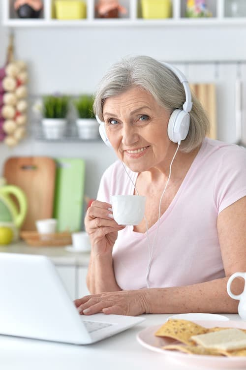 older lady wearing headphones and drinking coffee at laptop
