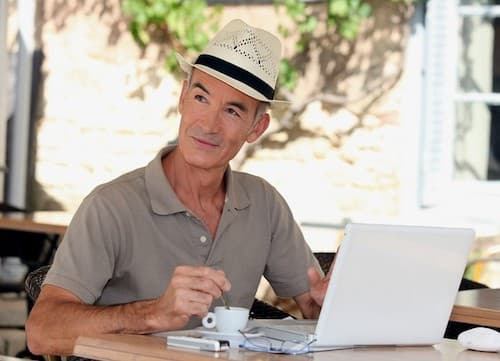 man wearing hat sitting at laptop and drinking coffee