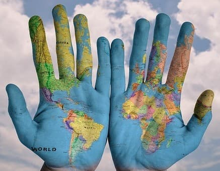 map of world printed onto two open hands