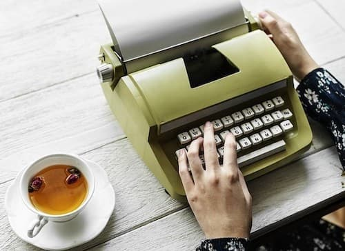 hands at old fashioned typewriter