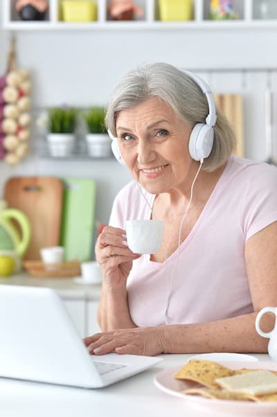 older lady sitting at a table with a laptop and wearing headphones