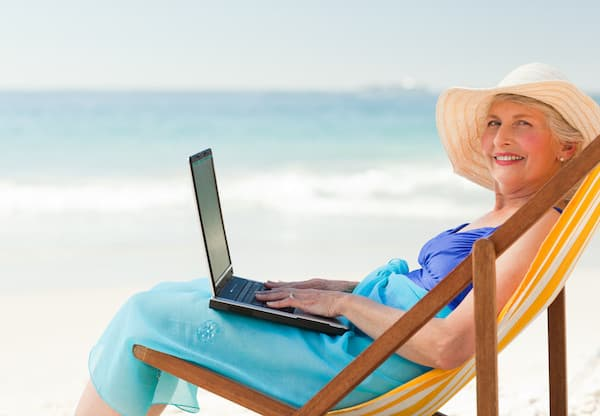 happy older lady with a laptop sitting on a deck chair at the beach